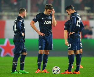 Wayne Rooney, Michael Carrick and Robin van Persie are downcast as they restart the game after conceding the first goal during the match against Olympiacos FC in Piraeus, Greece.  (Photo by Michael Regan/Getty Images)