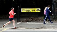 People are seen jogging past a social distancing sign in Dublin as the spread of the coronavirus disease (COVID-19) continues. April 21, 2020 REUTERS/Jason Cairnduff