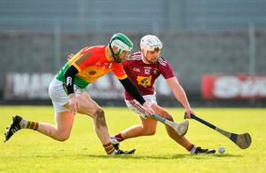 Robbie Greville of Westmeath and Carlow's Paul Doyle race for possession. Photo: Seb Daly/Sportsfile