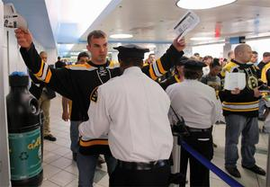 Fans are patted down as they enter the TD Garden before the start of an NHL hockey game between the Boston Bruins and Buffalo Sabres in Boston