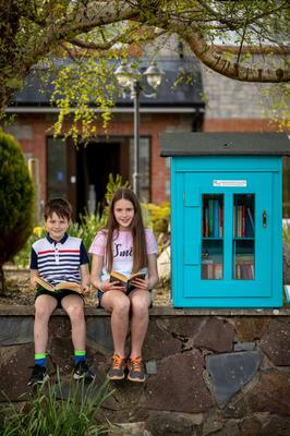 Book box: Cathal (8) and Emily (11) Phelan, from Callan, Co Kilkenny, sample the Little Free Library in the town that was set up by local man Barry Somers. Photo: Dylan Vaughan