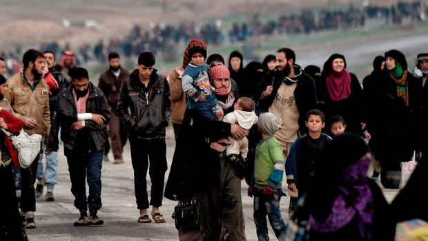 Exodus: Thousands of Iraqis walk down a road during their escape from Mosul this weekend as security forces try to retake the western parts of the city from Isil fighters. Photo: AFP/Getty