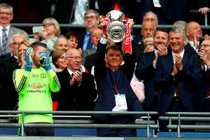 Manchester United boss Louis van Gaal lifts the FA Cup trophy at Wembley Stadium on Saturday. Photo: Getty