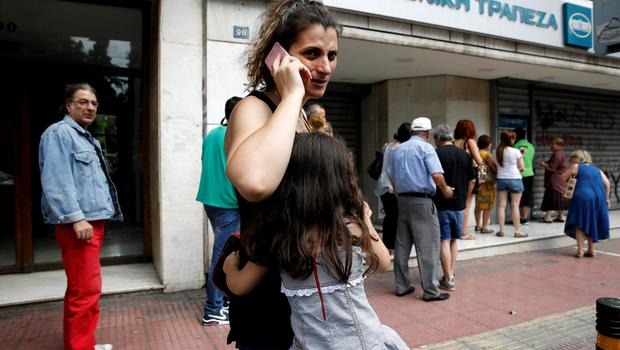 A young girl hugs her mother while lining up with other people to withdraw cash from an ATM outside a National Bank branch in Athens, Greece June 28, 2015. Greece said it may impose capital controls and keep its banks shut on Monday after creditors refused to extend the country's bailout and savers queued to withdraw cash, taking Athens' standoff with the European Union and the International Monetary Fund to a dangerous new level.  REUTERS/Alkis Konstantinidis