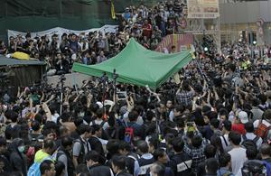 Workers start clearing away a tent set up by pro-democracy protesters at an occupied area in Mong Kok district of Hong Kong Tuesday, Nov. 25, 2014. (AP Photo/Vincent Yu)