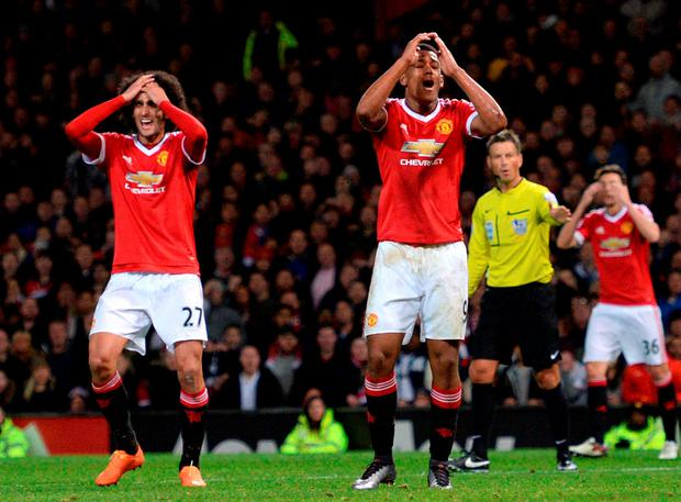 Manchester United's French striker Anthony Martial (C) reacts after missing a goal scoring opportunity during the English Premier League football match between Manchester United and West Ham United at Old Trafford in Manchester, north west England, on December 5, 2015.  AFP PHOTO / OLI SCARFF  RESTRICTED TO EDITORIAL USE. No use with unauthorized audio, video, data, fixture lists, club/league logos or 'live' services. Online in-match use limited to 75 images, no video emulation. No use in betting, games or single club/league/player publications.OLI SCARFF/AFP/Getty Images
