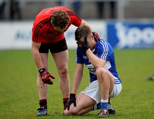 Down's Darren O'Hagan commiserates with Ross Munnelly of Laois after the final whistle