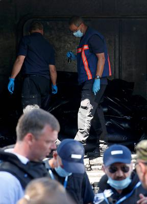 Monitors from the Organization for Security and Cooperation in Europe (OSCE) and members of a forensic team inspect a refrigerator wagon containing the remains of victims from the downed Malaysia Airlines Flight MH17, at a railway station in the eastern Ukrainian town of Torez. Reuters