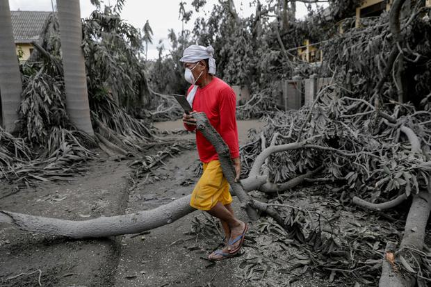 A worker carries a fallen branch in a resort blanketed with volcanic ash in Talisay, Batangas, Philippines, January 14, 2020. REUTERS/Eloisa Lopez
