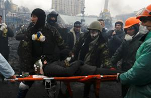Anti-government protesters carry an injured man on a stretcher after clashes with riot police in the Independence Square