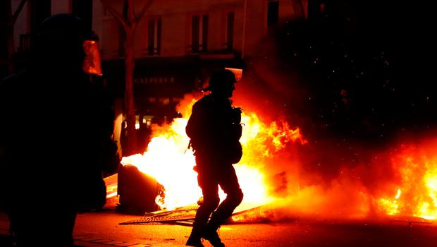 """Riot policemen walk near a fire during a demonstration by the """"yellow vests"""" movement in Paris, France, January 5, 2019. REUTERS/Gonzalo Fuentes"""