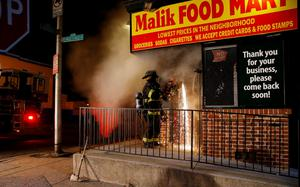 A Baltimore firefighter cuts his way into a burning convenience store with a saw to attack a fire set by rioters at East Biddle Street and Montford Avenue in Baltimore, Maryland in the early morning hours of April 28, 2015.  REUTERS/Jim Bourg