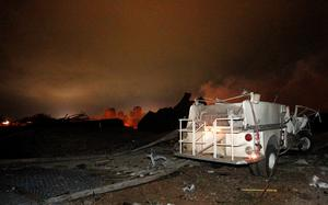 A vehicle is seen near the remains of a fertilizer plant burning after an explosion at the plant in the town of West, near Waco, Texas.