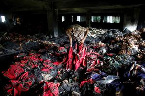 A garment worker inspects a factory belonging to Tung Hai Group, a large garment exporter, after a fire in Dhaka May 9, 2013. Eight people were killed when the fire swept through the garment factory in an industrial district of the Bangladeshi capital Dhaka, police and an industry association official said on Thursday. REUTERS/Andrew Biraj (BANGLADESH - Tags: DISASTER BUSINESS TEXTILE)