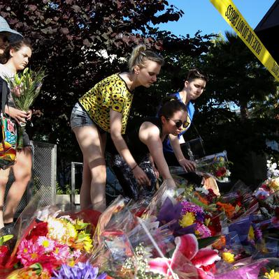 Visitors lay flowers on a makeshift memorial near the scene of a 4th-story apartment building balcony collapse in Berkeley, California