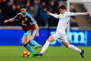 Swansea City's Tom Carroll attempts to tackle Burnley's George Boyd. Photo: PA