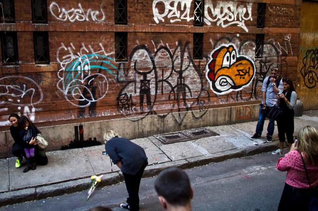 People gather to look at new artwork by British graffiti artist Banksy