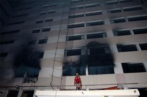 A fire fighter works to control the fire at a factory  in Dhaka