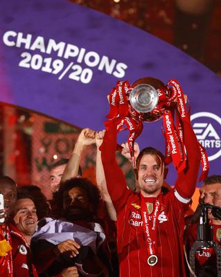 LIVERPOOL, ENGLAND - JULY 22: Jordan Henderson of Liverpool lifts The Premier League trophy following the Premier League match between Liverpool FC and Chelsea FC at Anfield on July 22, 2020 in Liverpool, England. Football Stadiums around Europe remain empty due to the Coronavirus Pandemic as Government social distancing laws prohibit fans inside venues resulting in all fixtures being played behind closed doors. (Photo by Phil Noble/Pool via Getty Images)
