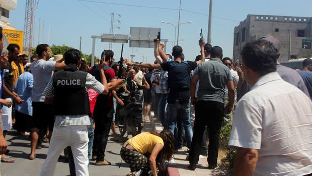 Police officers try to control the crowd after a gunman opened fire at a beachside hotel in Sousse, Tunisia, June 26, 2015. A gunman disguised as a tourist opened fire at a Tunisian hotel on Friday with a weapon he had hidden in an umbrella, killing tourists, including those from Britain, Germany and Belgium, as they lounged at the beach and pool in the popular resort town. The death toll from the shooting attack has risen to 37, the health ministry said in a statement carried by state news agency TAP. REUTERS/Amine Ben Aziza