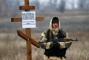 An armed security representing the self-proclaimed Donetsk People's Republic stands guard near a cross erected by local residents in memory of victims as members of the recovery team work at the site where the downed Malaysia Airlines flight MH17 crashed outside the village of Rozsypne (Rassypnoye), eastern Ukraine (REUTERS/Maxim Zmeyev)