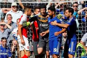 Arsenal's defender Gabriel and Chelsea's Diego Costa are separated by Arsenal's Czech goalkeeper Petr Cech as they clash during match