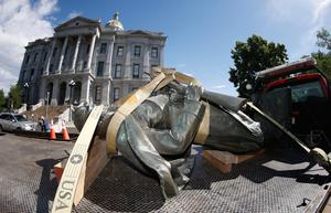 The Civil War Monument statue is strapped on the back of a flatbed tow truck after it was toppled from its pedestal in front of the State Capitol in Denver, Colorado. AP Photo/David Zalubowski