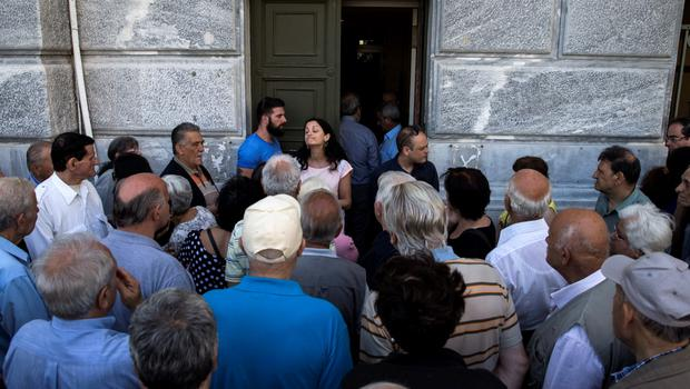 People, most of them pensioners, argue with a staff member outside a closed National Bank branch at the bank's headquarters in Athens, Greece June 29, 2015.  REUTERS/Marko Djurica