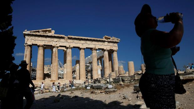 A woman takes a drink in front of the Parthenon temple atop the Acropolis hill in Athens June 18, 2015. Hopes of a breakthrough at Thursday's gathering of European finance ministers, once seen as the last opportunity for an agreement, looked increasingly remote. REUTERS/Paul Hanna