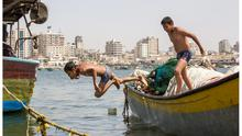 Boys swimming in Gaza port near where test rockets were fired earlier this week. Photo: Mark Condren