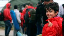 A migrant child gives a thumbs-up as he arrives to a newly erected refugee camp in the Croatian town of Opatovac, 20 kms from Tovarnik, on September 20, 2015. The camp has 200 tents, each with a capacity of housing 24 people. Migrants are still mostly gathered on Croatia's main border crossings with Slovenia, seeking transit through Slovenian territory in their bid to travel to northern Europe.  AFP PHOTO / STRINGERSTRINGER/AFP/Getty Images