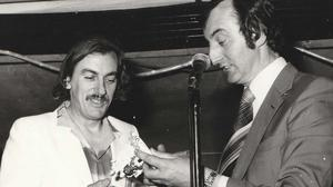 P.J. O'Gorman, Director of the Song of the South International Song Contest at the 1984 Charleville Cheese Festival, presenting compere Shay Healy with a piece of Dromcollogher Dresden
