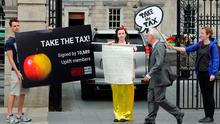 Taxing times: A protester dressed as Snow White demonstrates outside the parliament buildings in Dublin in support of the EU ruling to take €13bn in taxes from Apple last September