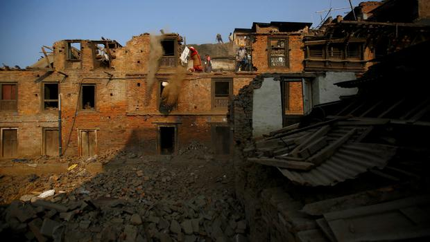 People manually demolish the wreckage of collapsed houses following the April 25 earthquake in Bhaktapur, Nepal, June 5, 2015. REUTERS/Navesh Chitrakar
