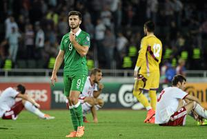 Shane Long surveys the scene among disconsolate Georgia players at the final whistle. Picture credit: David Maher / SPORTSFILE