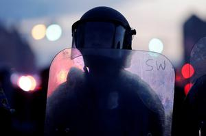 A police officer stands guard Monday, April 27, 2015, after rioters plunged part of Baltimore into chaos, torching a pharmacy, setting police cars ablaze and throwing bricks at officers.  (AP Photo/Matt Rourke)