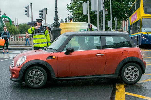 A Garda stops a motorist who had turned right on to O'Connell Bridge from the north quays yesterday. Photo: Kyran O'Brien