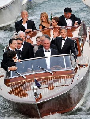 Actor George Clooney, right, waves from a boat with Ramzi Alamuddin, third from right front row, father of her fiancee Amal Alamuddin, his father Nick Clooney, fifth from right front row, and his mother Nina Bruce, second from right back row on their way to the Aman hotel ahead of his wedding