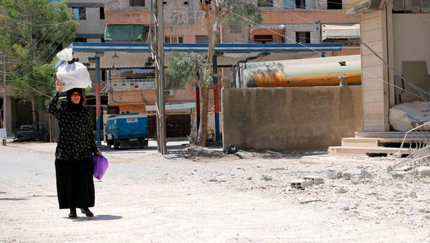 A woman carries her belongings as she walks at a site hit by what activists said was an airstrike by forces loyal to Syria's President Bashar al-Assad, at the eastern Ghouta of Damascus June 5, 2015. REUTERS/Amer Almohibany