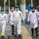 Ambulance crew members in protective gear walk with workers at a community health station in Wuhan (Chinatopix via AP)