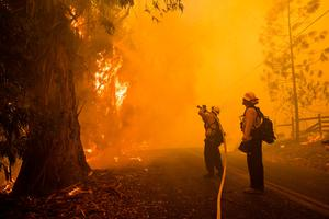 In this file photo taken on October 27, 2019 firefighters battle the Kincade Fire along Chalk Hill Road in Healdsburg, California on October 27, 2019. Photo by Philip Pacheco / AFP