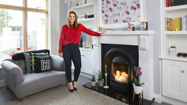 Entrepreneur Nicki Hoyne in her front room. She installed the units flanking the mantelpiece. The colourful cushions on the love seat from Loaf are by Christian Lacroix, while the initial cushion is from Etsy. The photograph is by Gray Malin and Nicki bought the little Karl Lagerfeld and his companion in Brown Thomas. Photo: Tony Gavin