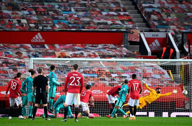 Bruno Fernandes of Manchester United scores their side's third goal past Alisson Becker of Liverpool from a free kick. (Photo by Laurence Griffiths/Getty Images)