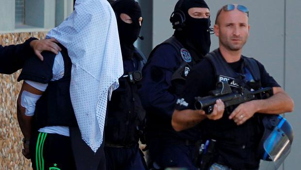 REFILE ADDING DISCLAIMER    A man supposed to be the suspect who held over an attack against a gas company site is escorted by police officers during investigations in Saint-Priest, near Lyon, France, June 28, 2015.  Yassin Salhi, 35, told detectives he had killed Herve Cornara in a parking area before arriving at the plant in Saint Quentin-Fallavier, 30 km (20 miles) south of Lyon, where he attempted to cause an explosion on Friday, the source told Reuters.  REUTERS/Emmanuel Foudrot    ATTENTION EDITORS FRENCH REQUIRES THAT FACES SPECIAL INTERVENTION POLICE FORCES ARE MASKED IN PUBLICATIONS WITHIN FRANCE