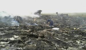 In this image taken from video, Thursday July 17, 2014,  people walk amongst the debris at the crash site after a passenger plane carrying 295 people was shot down Thursday as it flew over Ukraine, near the village of Hrabove, in eastern Ukraine. AP Photo / Channel 1