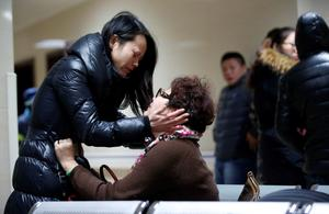 Relatives of a victim hug as they wait at a hospital where injured people of a stampede incident are treated in Shanghai January 1, 2015. REUTERS/Aly Song