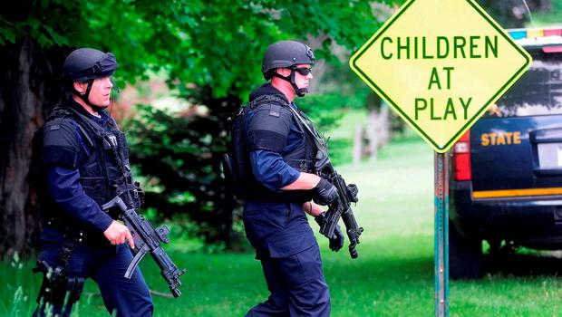 Two law enforcement officers make their way across a lawn and onto Pleasant Street on Wednesday, in Dannemora, New York. Photo: AP