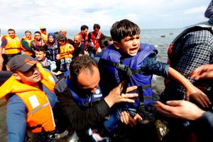 A Syrian refugee child is carried off an overcrowded dinghy on the Greek island of Lesbos, after crossing a part of the Aegean Sea from Turkey. Photo: Reuters