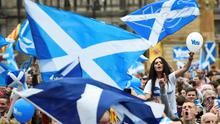 Campaigners wave Scottish Saltires at a 'Yes' campaign rally in Glasgow yesterday
