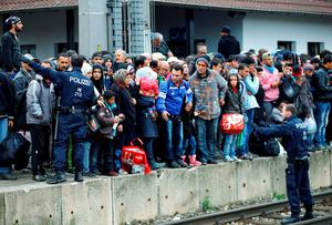 Police try to keep order as refugees gather at Nickelsdorf station in Austria. Trains to Germany were cancelled, forcing many to make the long trek over the border on foot with their family and belongings